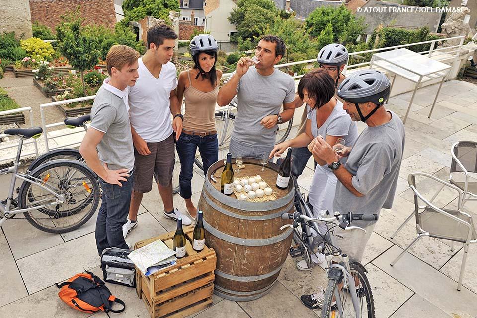 Cyclotouristes degustant des crottins de Chavignol et du vin, dans le vignoble de Sancerre.